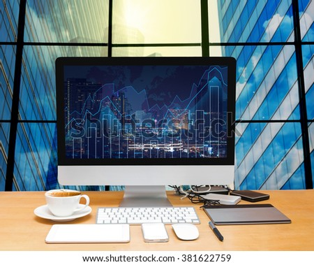 Workspace with computer desktop on the wood table with trading graph at the screen on the blurred photo of cityscape building background