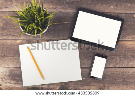 workspace with digital tablet, phone and blank paper on wooden table - stock photo