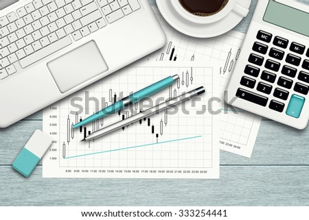 workspace with graph, computer, graph, calculator and stationery over blue desk - stock photo