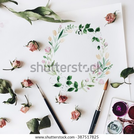 Workspace. Wreath frame with flowers and leaves painted with watercolor, paintbrush and pink roses isolated on white background. Overhead view. Flat lay, top view - stock photo