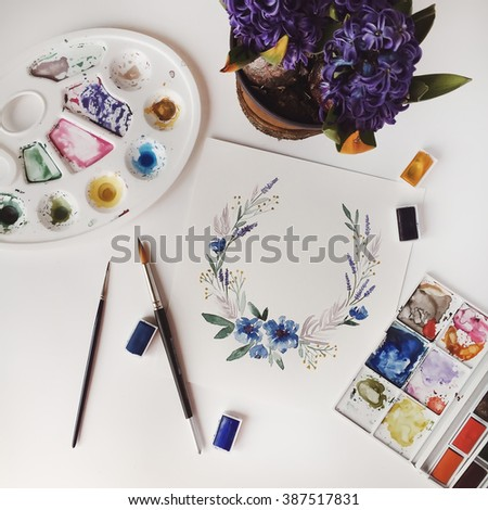 Workspace. Wreath with blue flowers and leaves painted with watercolor, paintbrush and flowers in flowerpot isolated on white background. Overhead view. Flat lay - stock photo