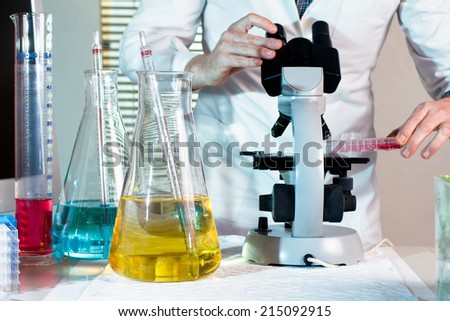 worktable research laboratory with scientific examining a sample under the microscope - stock photo