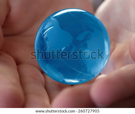 world, earth, planet, business concept - blue glass earth  globe in the hands   - stock photo