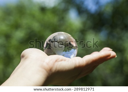 World environmental concept. Crystal globe in human hand on beautiful green and blue bokeh. Visible are the continents the Americas. Selective focus on the reflection. - stock photo