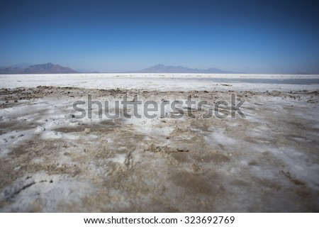 World famous Bonneville Salt Flats outside Salt Lake City Utah with mountains and blue skies. Detail of the salt on the ground - stock photo