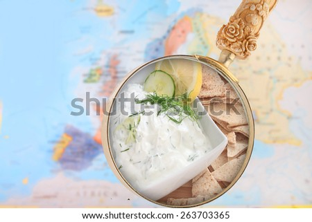 World foods showing Europe with magnifying glass looking in tzatziki sauce or dip from Greece - stock photo