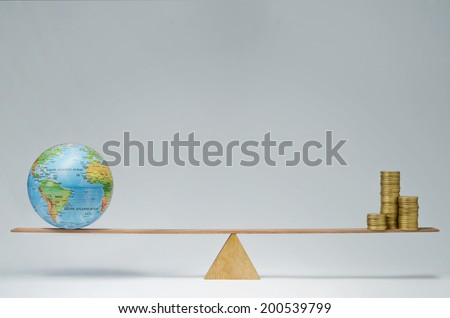 World globe and money coins stack balancing on a seesaw - stock photo