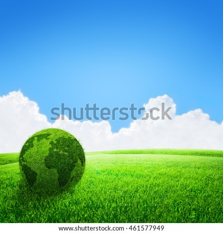 World globe shape of green grass in field and blue sky background