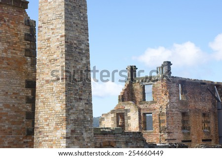 World Heritage Site of  Port Arthur Convict Museum Settlement in Tasmania, Australia, with ruins of historic prison and other buildings, tourist attraction, blue sky and copy space. - stock photo