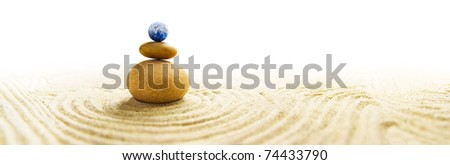 World in balance - Stone pile in a Zen Garden with a miniature Earth globe as topmost stone - stock photo