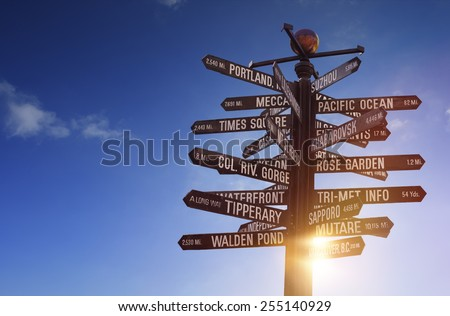 World Landmarks Signpost containing various famous places all over the world, with blue sky, sun shining through the object and free copy space for your text - stock photo