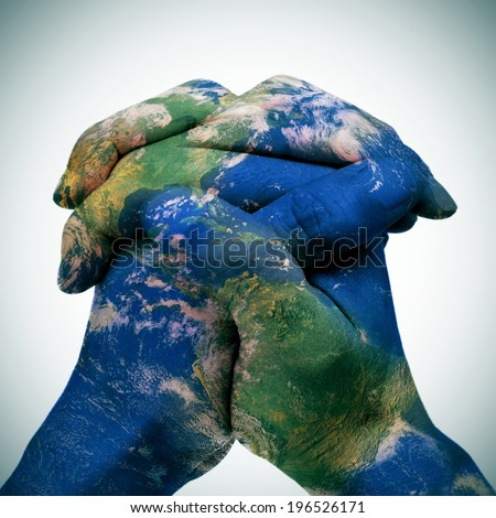 world map in the clasped hands of a man forming a globe (Earth map furnished by NASA) - stock photo