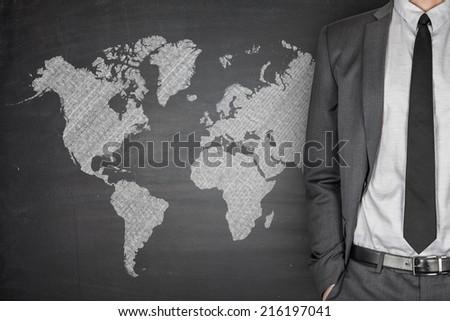 World Map on black Blackboard with businessman - stock photo