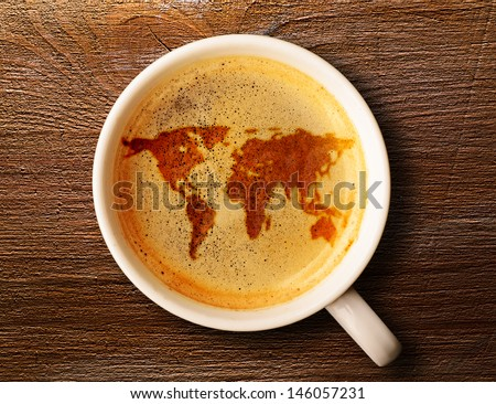 world map on cup of fresh espresso on table, view from above - stock photo