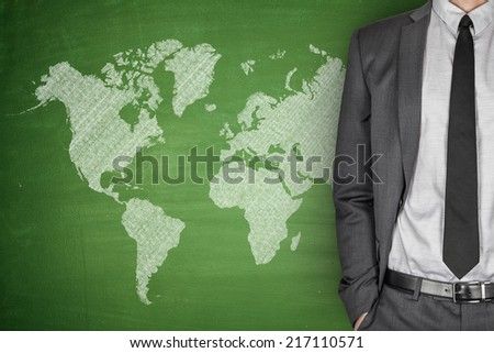 World Map on green Blackboard with businessman - stock photo