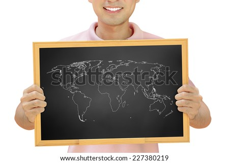 World map outline on blackboard held by smiling man - stock photo