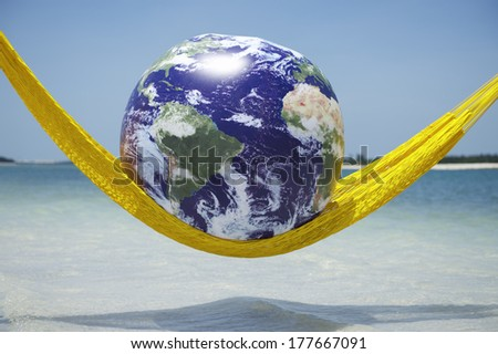 World relaxing in bright yellow hammock above tropical beach sea  Elements of this image provided by NASA - stock photo