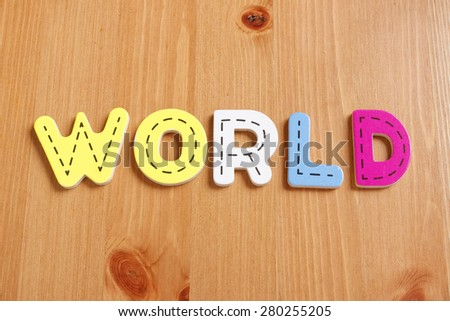 WORLD, spell by woody puzzle letters with woody background - stock photo