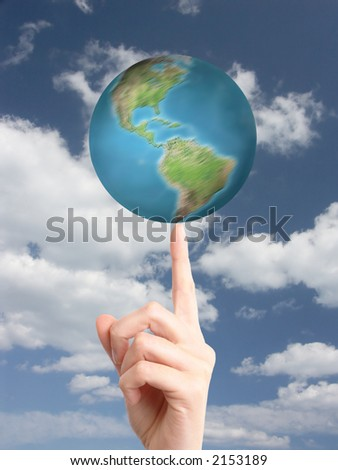 World spinning on index fingertip against cloudy sky - stock photo