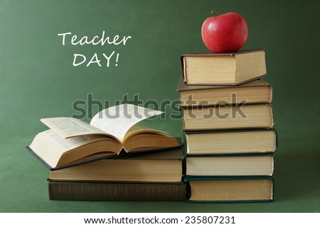 World Teacher's Day (still life with book pile, apple and desk on artistic background) - stock photo