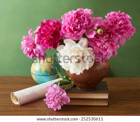 World Teacher's Day (still life with peony flowers bunch, books, map and globe on artistic background) - stock photo