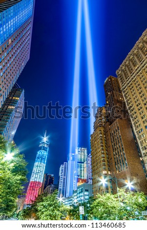 World Trade Center Lights and Freedom Tower at night in Manhattan - American flag colors of red white and blue on the famous skyscraper commemorating September 11th - stock photo