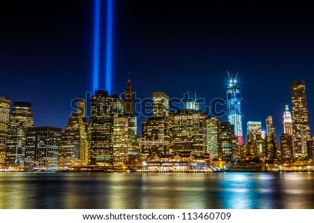 World Trade Center 911 Lights over Manhattan buildings off East River at night in New York City - stock photo