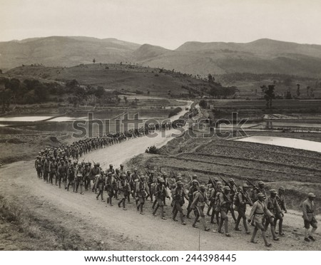 World War II. Chinese soldiers marching on the Burma Road toward the fighting lines on the Salween River front. 1943 photo by Frank Cancellare. - stock photo