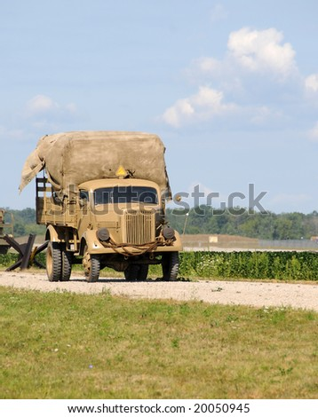 World War II era army truck on a dusty road - stock photo