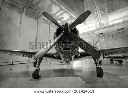 World War II era fighter plane in a hangar - stock photo