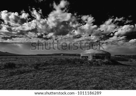 World war two bunker in the country under a dramatic sky in black and white