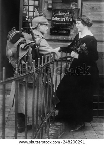 World War 1. Young German couple saying goodbye. The soldier wears his uniform with full gear including his backpack and rifle. Ca. 1914. - stock photo