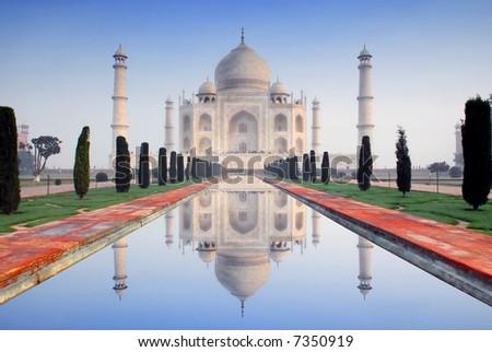 world wonder taj mahal in soft early morning light with blue sky - stock photo