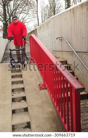 Worms, Germany - December 1, 2010: Old man having difficulties to move barrier-free though his city - stock photo