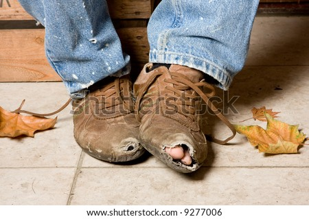 Worn and battered shoes of a beggar in the streets - stock photo