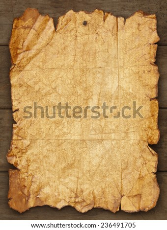 Worn and Ripped Paper Tacked on Wood Background with Copy Space. - stock photo