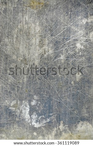 worn and scratched flat piece of steel as a grungy, textured background in silver gray tones. There are random splotches of wear and deep scratches on the surface. Vertical composition. - stock photo