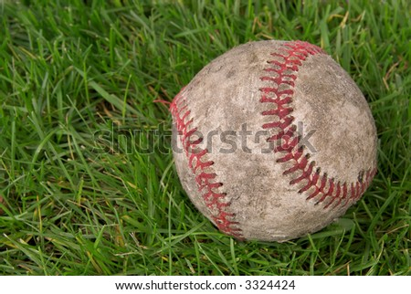 worn,dirty baseball in grass with a white background - stock photo
