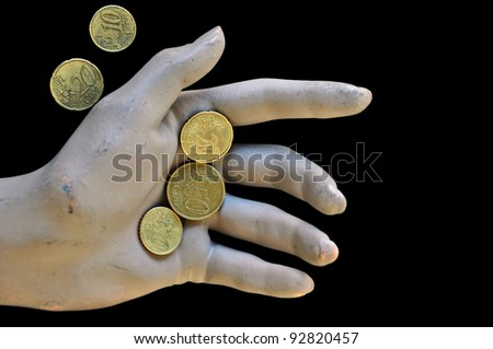 Worn doll hand holding euro coins. Economic and financial issues. - stock photo