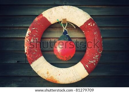 Worn down lifebuoy and flotation device awaiting their next use - stock photo