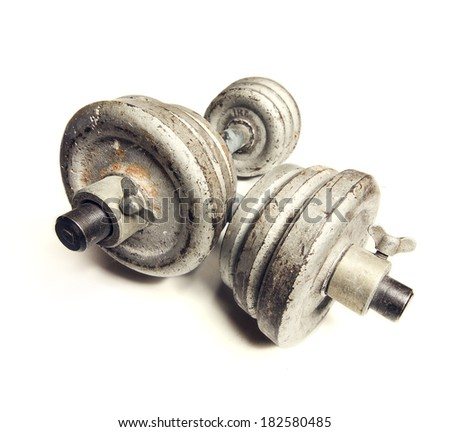 Worn old dumbbell on a white background close-up. - stock photo