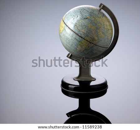 worn, old looking globe on black with reflection