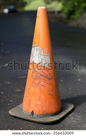 Worn out bright orange traffic cone placed on the middle of tarred country road. Background has out of focus green vegetation and road surface.  - stock photo