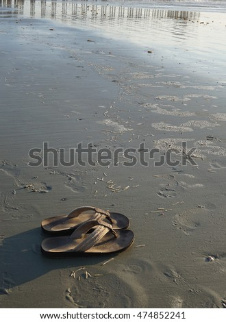 Worn out foot  wear on sand/Leather Sandals/Shoes on sand