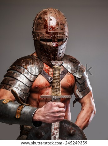 Worn out gladiator after fight holding shield and sword - stock photo