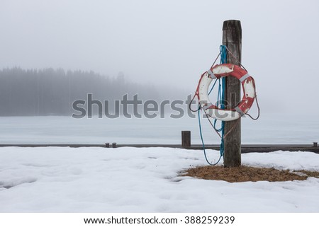 Worn-out lifesaver on post at foggy lake scape - stock photo