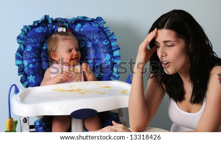Worn-out mother with crying baby - stock photo