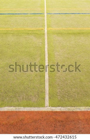 Worn out plastic hairy carpet on outside hanball court. Floor of sports playground with colorful marking lines.