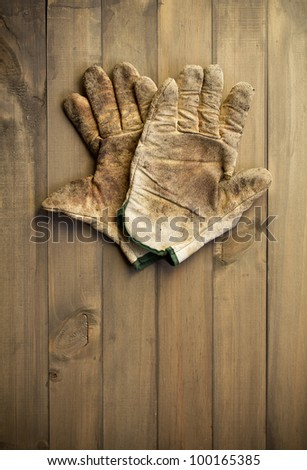 worn out working gloves against wooden surface. add your text - stock photo