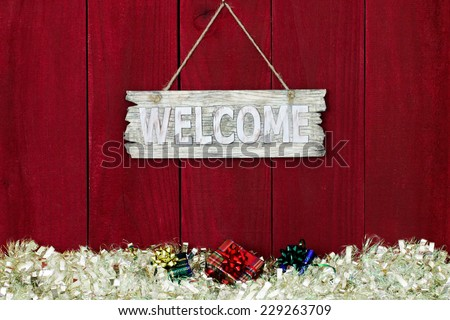 Worn wood welcome sign with white garland Christmas border with presents hanging on antique red wooden background - stock photo